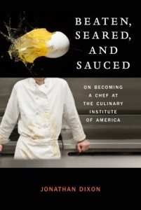 In the upper third a breaking egg shoots across a black background, in the lower two thirds a chef leans against the counter, shown from neck to waist